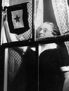 Original caption:Mrs. John Gagne of Lynn (MA), proudly places the gold star service flag in the window in her home, following the news of the death of her son, a member of the U.S. Army Corps, who was killed in action during a bombing of Hickam Field in Hawaii, by Japanese bombers. She is the first Gold Star Mother in this city in World War II.