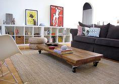 la mesa de madera rustica, el puf y la alfombra combinan muy bien con lo contemporáneo de los cubos blancos, la silla y los cuadros de corte pop. Por su parte, el sofá está muy bien elegido, cohesiona ambos estilos.