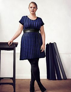 The season's hottest skater silhouette is a versatile favorite in houndstooth. Seamed to flatter curves and fitted with a scoop neck and patent skinny belt. Short sleeves.  lanebryant.com