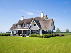 Mooi landhuis met rieten dak witte gevels en Antraciete kozijnen