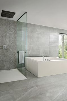En grå klinkerplatta med stenuttryck på både vägg och golv ger en clean känsla i badrummet.
