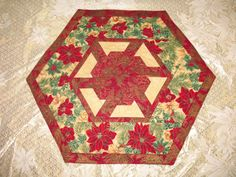 "Reversible table topper is quilted with a meandering stitch in gold embroidery thread on beautiful poinsettia, red and gold fabrics from Hoffman California lined with interlining to prolong durability and shape.  * Measures 17"" x 19.75""  Tie in the theme of your rooms with coordinating placemats available here  https://www.etsy.com/listing/109751568/placemat-winter-impressions-reversible-4 --- #quiltsyteam"