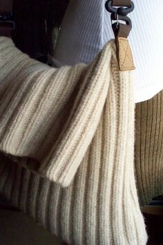 Recycled Sweater Messenger Style Purse - fold-over flap design with recycled adjustable, swivel strap with leather tabs.    A simply-styled, reconstructed purse. Theres a stiff piece of fiber board in the bottom. No lining. Nothing fancy, just perfectly reusable!    100% wool in natural Aran or off-white.  Cotton webbing strap.  Measures approximately 12 wide by 16 long, when laid flat and 12 X 10 when folded over.    (The last photo shows both of the bags made from this sweater. Only the…