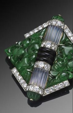 Property of various owners An art deco jadeite jade, moonstone, black onyx and diamond brooch, Mauboussin, French, circa 1925 signed Mauboussin France, with French assay marks; estimated total diamond weight: 2.00 carats; mounted in platinum-topped eighteen karat gold; dimensions: 1 3/4 x 1 3/4in.