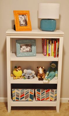 Bookshelf and baskets - combining blue and orange accessories onto white furniture, fabric baskets. Must look out/make orange and turquoise picture frames
