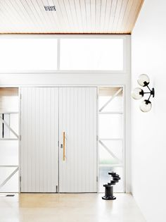 Painted white wood door in entryway with modern wall sconce, wood ceiling and bright natural light