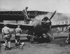 US Marine ground crew putting out a fire on a Wildcat fighter, Henderson Field, Guadalcanal, Solomon Islands, 1942, WWII