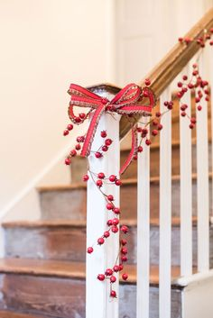 CHRISTMAS DECORATIONS THEME: ENCHANTED FOREST. For a beautiful staircase display, drape V V Rouleaux's peonie red rosehip garlands, or in fact any of our garlands, and finish with a Christmas ribbon double bow.