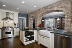 love the exposed brick arches between the kitchen and family room