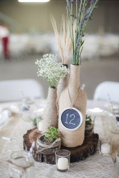 Rustic centerpiece - twine wrapped bottles with clever use of chalkboard paint on mason jar lids