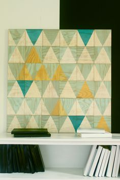 teal, aqua and yellow, triangle composition of wooden tiles, magnetic on the wall to rearrange when desired.