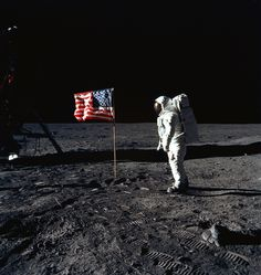 NASA astronaut Buzz Aldrin stands next to the American flag planted on the moon during the first moon landing.