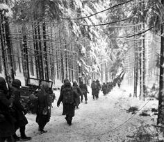 American soldiers march along the snow-covered road on their way to cut off the Saint Vith-Houffalize road, Belgium.