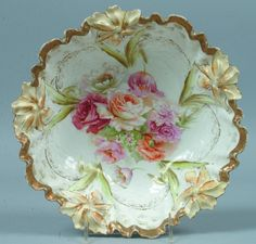 """RS Prussia Bowl, 10.5""""d.; Mold 28a, Carnation variant FD 15, foral design to center with inner gold stenciled border, checkerboard gold treatment to inner wall, naturally colored mold rim flowers and heavy gold ribbon rim"""