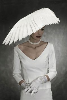 A bridal design by British fashion designer, Jess Eaton.  Eaton uses white feathers and whole wings of birds to create extravagant headpieces, which are inspired by films, fairy stories and books from her childhood.