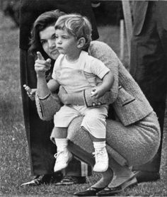 John F. Kennedy, Jr. watches from the rose garden with his mother, Jacqueline Kennedy, as his father gives a formal greeting to Algerian Premier Ahmed Ben Bella during ceremony on the White House grounds in Washington in 1962.