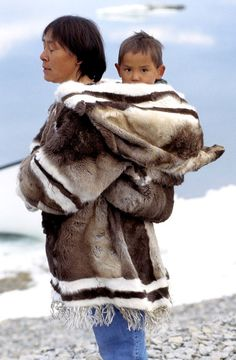 Inuit infants are carried by their mothers in an amautik for the first year or two of their lives. An amautik was traditionally made from caribou fur, with the fur facing in, so the baby lay in its comfort and warmth. Today, they are also made from duffel and other materials. - Photo by Ansgar Walk and Survival International (www.survivalinternational.org), found via The Huffington Post