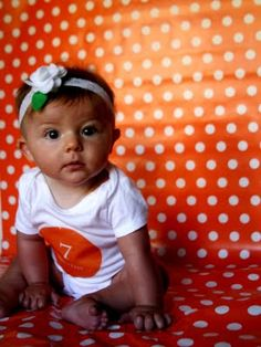 Monthly baby pictures using wrapping paper for backdrop.
