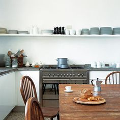 Simple, neat, and tidy. I love the contrast of the white walls, gray range,  modern shelving, and wooden table.