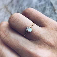 A teeny opal is prong set and topped with five prong set cz stones.Brass base14K yellow gold plated4.1mm lab created opalFive CZ stones range 1-1.5mmProng setting1.02mm band thicknessNickel free