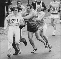 "Katherine Switzer defying societal odds.  In 1967 a race official tried to remove Katherine Switzer from the Boston Marathon only to be pushed aside by marathon runners. Women were considered ""too fragile"" for the marathon at the time and were prohibited from running. Switzer completed the race."