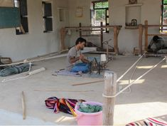 Spinning wool at #VankarVishramValji weaving workshop in Gujarat. The traditional pit looms can be seen in the background. http://stitchbystitch.eu/blog/2013/11/6/visit-to-a-gujarati-master-weaver