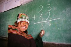 A smiling girl does arithmetic at the blackboard in a UNICEF-assisted local primary and secondary school in Pisili, an indigenous Ayllu Yampara settlement in the south-central department of Chuquisaca, near the town of Tarabuco, capital of Yamparáez Province in Bolivia. UNICEF supports a child-friendly education project for indigenous girls in Chuquisaca Department.  © UNICEF/Giacomo Pirozzi  http://www.unicef.org