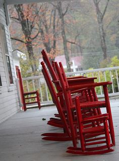 Red rocking chairs on a covered front porch....relaxing!~~~ I can see these on your porch up at Camp Wilburn, Sister! <3