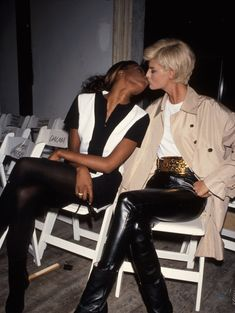 Naomi Campbell and Linda Evangelista kissing in the front row of a fashion show