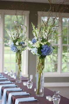 These tall rustic centerpieces look beautiful with the mixture of blue, green, white and brown. Photographer: Jeff Greenough