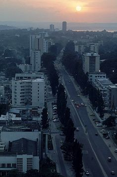 Scene of downtown Kinshasa, the capital of Congo, showing the main street, the 20th Juin, cutting through the city at sunset.