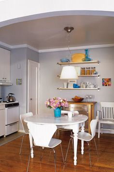 Ikea wall shelves, installed high up, to emphasize ceiling height, while adding storage space