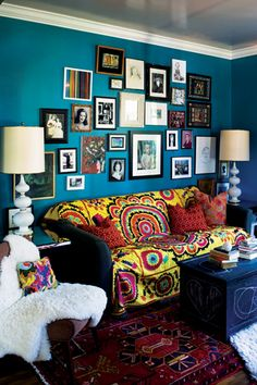 living room, blue walls, prints, framed photos of walls, tall side table lamps, sheep skin on chair, tribal rug, printed pillows