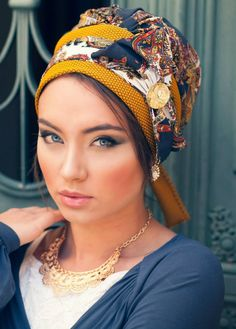 Pre-sewn turban with a large bow at the front! This gorgeous turban is made of a combination of mustard and navy-patterned fabrics. The turban is intricately sewn to create the shape of a turban- all you need to do is place it on your head and tie! This h