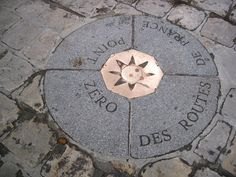 Point Zero Roads France is represented by a slab four quarters in the center of which is placed a hexagonal medallion representing a compass. It is from this point that are calculated in kilometers, distances between Paris and other cities of France. This zero point is located on the front of Notre-Dame de Paris. As the Trevi Fountain in Rome, some tourists, probably without giving specific meaning to their actions, throw a piece of pennies of Euro in this case, on the medallion.