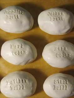 DIY place card rocks made from clay using stamps. cute, but it would take forever to do for 100 people!