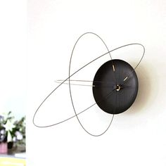 The Orbits Clock, A Wall Clock With Rotating Carbon Fiber Circles for Hands