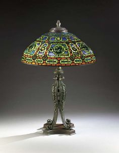 A 'ZODIAC' LEADED GLASS, TURTLEBACK TILE AND BRONZE TABLE LAMP   TIFFANY STUDIOS, CIRCA 1910   32 7/8in. (83.5cm.) height including finial, 22¼in. (56.5cm.) diameter of the shade  the shade stamped TIFFANY STUDIOS NEW YORK 1808, the base unsigned