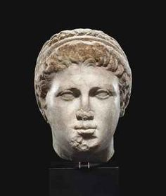 A GREEK MARBLE HEAD OF A YOUTH  HELLENISTIC PERIOD, CIRCA LATE 4TH-EARLY 3RD CENTURY B.C.  Depicted with a smooth round face, his heavy-lidded almond-shaped eyes slightly convex, the bridge of his nose merging with his gently-arching brows, with a small mouth and full lips, his wavy locks brushed forward and bound in a diadem, covering the tops of his ears, with an upturned fringe along his forehead, breaking to the right and left at the center  8 1/8 in. (20.7 cm.) high