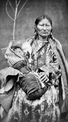 Studio portrait (sitting) of Spotted Tail's wife and baby, Native American (Brulé Sioux) woman and child. She wears a dress and blanket shawl. The baby is wrapped in swaddling clothes and blankets. Date [between 1875 and Native American Beauty, Native American Photos, Native American Tribes, Native American History, American Indians, Art Indien, Indiana, By Any Means Necessary, Indian Pictures