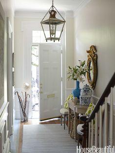 Gilded eagle mirror in entry. Design: Lynn Morgan. Photo: Christopher Baker. housebeautiful.com. #antiques #gildedmirror #lantern #entry #rowhouse #enterinstyle