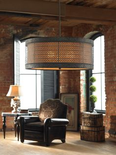 Metal filigree with detailed banding finished in a semi matte black with rust antiquing holds the separate interior shade of silken warm beige fabric.