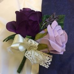 A silk buttonierre featuring purple & lilac roses plus ivory lace