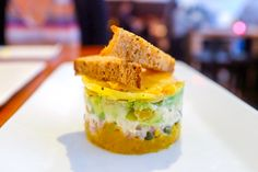 Yellow beets roasted on a bed of salt and then sliced and minced as the base of a cylindrical rettine layered with avocado, smoked tofu, capers, red onion, and cucucmbers creamy from vegan mayonnaise.