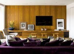 A parede foi revestida com a mesma madeira do móvel, aquecendo a sala. O ambiente foi projetado pela arquiteta Vanessa Féres (Foto: Edu Castello e Maíra Acayaba/Editora Globo)