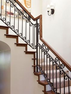 """When it comes to staircases, nothing says """"Old World"""" better than balustrades that combine wood and iron. Here, the black ironwork repeats the metal finishes seen in the home's light fixtures and furnishings; the ironwork's scrolled design softens the staircase's straight lines and hard edges and subtly reflects the curvy contours of the home's arched doorways."""