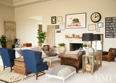 Leather sofa, white slipcovered couch, navy wing chairs and leather club chairs. Love the eclectic mix