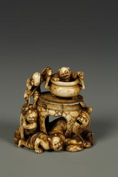 JAPANESE IVORY NETSUKE OF A A DEMON CATCHER AND SEVERAL ONI, the demon catcher crawling under a table with several oni playing havoc, signed Masamitsu/Shokou