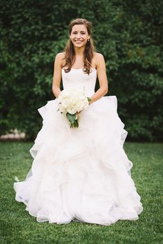 Sarah styled her hair half-up with loose curls. She was beautiful in a strapless ball gown featuring a fitted bodice and ruffled skirt. Photography: James Christianson Read More: http://www.insideweddings.com/weddings/summer-destination-wedding-with-rocky-mountain-views-in-aspen-co/642/