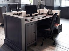 A reception with a black-brown solid wood desk and a black swivel chair on castors